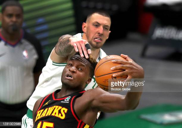 Boston Celtics center Daniel Theis reaches over the head of Atlanta Hawks center Clint Capela for a rebound in the fourth quarter under the Hawks...