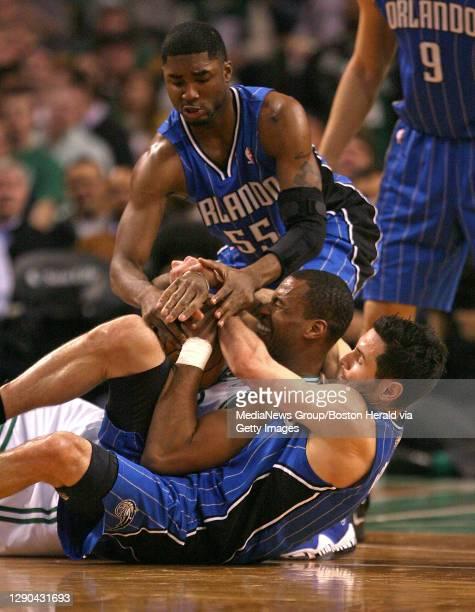 Boston Celtics center Jason Collins wrestles with Orlando Magic shooting guard J.J. Redick and Orlando Magic shooting guard E'Twaun Moore for the...