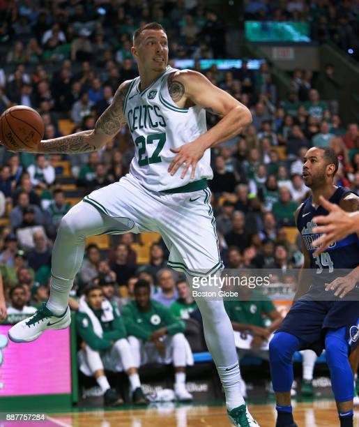 Boston Celtics' Daniel Theis saves a ball from going out of bounds under the basket during the first half The Mavericks' Devin Harris is at right The...