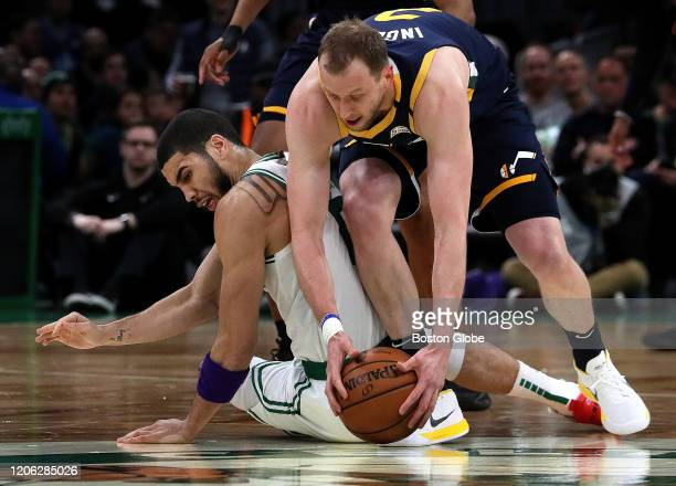 Boston Celtics forward Jayson Tatum and Utah Jazz guard Joe Ingles chase a loose ball during the first quarter. The Boston Celtics host the Utah Jazz...