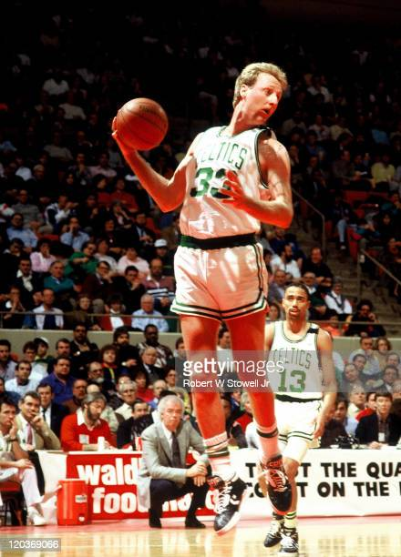 Boston Celtics forward Larry Bird looks up court after rebounding ball during a basketball game Hartford CT December 1991 Guard Charles Smith looks on