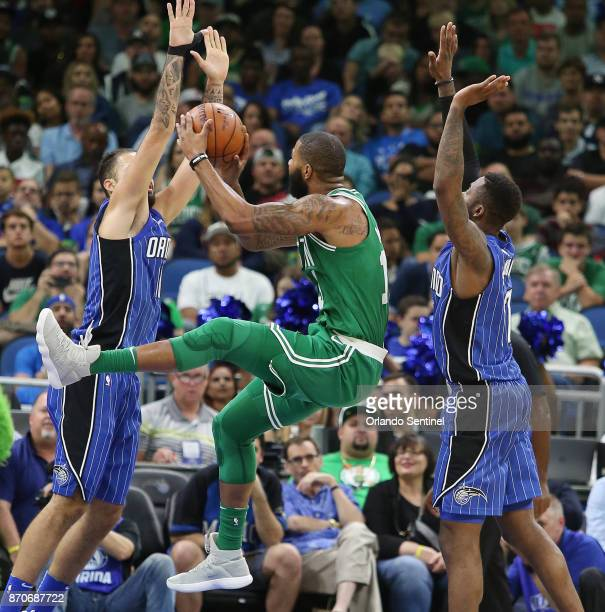 Boston Celtics forward Marcus Morris takes a shot between Orlando Magic players Evan Fournier and Jonathon Simmons on Sunday Nov 5 2017 at the Amway...
