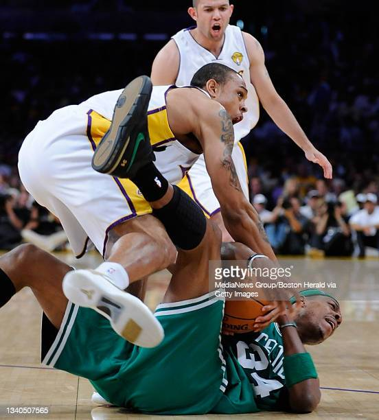 Boston Celtics forward Paul Pierce falls to the court as he battles for a loose ball with Los Angeles Lakers guard Shannon Brown, left, and Los...