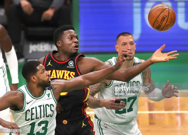Boston Celtics forward Tristan Thompson , left, and Boston Celtics center Daniel Theis , right, battles Atlanta Hawks center Clint Capela for a...