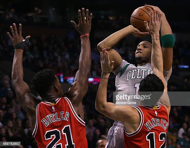 Boston Celtics guard Evan Turner drains a shot as he is defended by Chicago Bulls guard Jimmy Butler and Chicago Bulls guard Kirk Hinrich during the...
