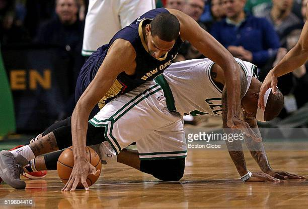 Boston Celtics guard Isaiah Thomas appears to hurt himself as he and New Orleans Pelicans center Alexis Ajinca and Boston Celtics guard Avery Bradley...
