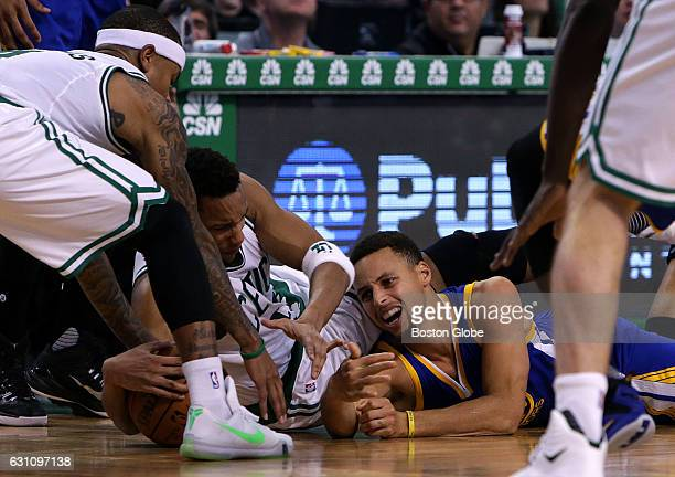 Boston Celtics guard Isaiah Thomas Boston Celtics guard Evan Turner and Golden State Warriors guard Stephen Curry hit the parquet as they fight for a...