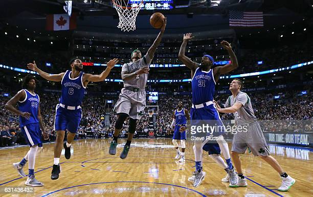 TORONTO ON JANUARY 10 Boston Celtics guard Isaiah Thomas lays up the ball between Cory Joseph and Terrence Ross as the Toronto Raptors wearing their...