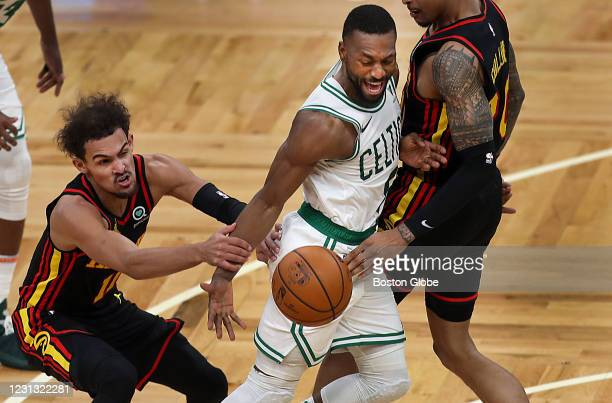 Boston Celtics guard Kemba Walker is sandwiched between Atlanta Hawks guard Trae Young , left, and Atlanta Hawks forward John Collins as he drives...