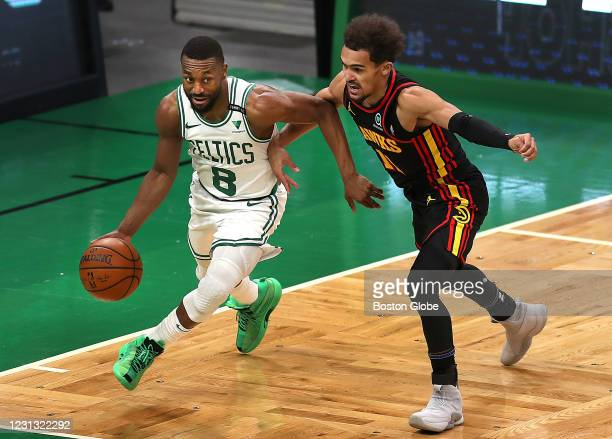 Boston Celtics guard Kemba Walker , left, drives under the Celtics basket pursued by Atlanta Hawks guard Trae Young . The Boston Celtics host the...