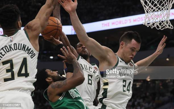 Boston Celtics guard Kyrie Irving is stuffed by Milwaukee Bucks guard Eric Bledsoe and Milwaukee Bucks forward Giannis Antetokounmpo as he tries to...