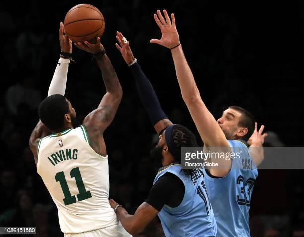 Boston Celtics guard Kyrie Irving makes a pull up jump shot over Memphis Grizzlies guard Mike Conley and Memphis Grizzlies center Marc Gasol for a...