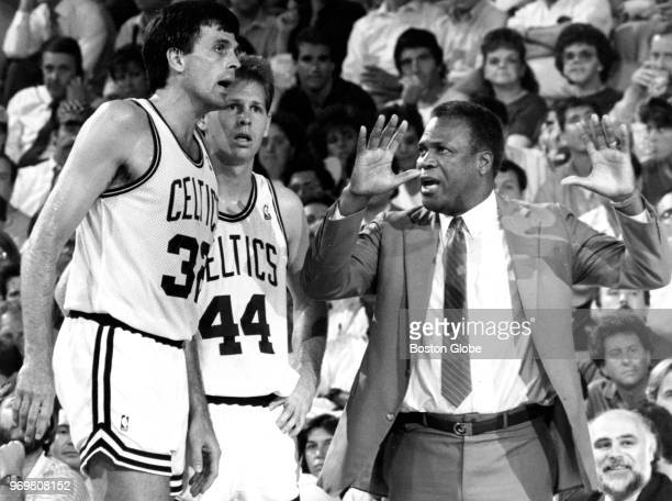 Boston Celtics head coach KC Jones gestures as he talks with players Kevin McHale left and Danny Ainge during Game Five of the third round of the...