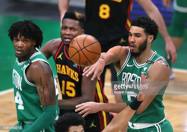Boston Celtics' Jason Tatum fires a pass in the second quarter as Celtics' Robert Williams and Atlanta Hawks' Clint Capela fight for the position...
