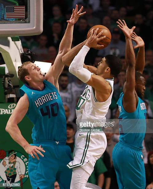 Boston Celtics' Jayson Tatum drives to the basket with pressure from Charlotte Hornets' Cody Zeller and Kemba Walker during the fourth quarter The...