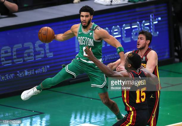 Boston Celtics' Jayson Tatum grabs a rebound and makes a pass in the second quarter under the Celtics basket, as Atlanta Hawks' Clint Capela defends....