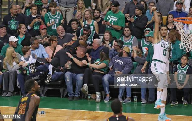 Boston Celtics Jayson Tatum scores a threepoint basket as Cleveland Cavaliers LeBron James watches from the front row of the seats during the first...