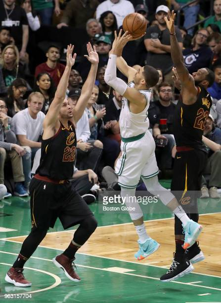 Boston Celtics Jayson Tatum shoots a jump shot with pressure from Cleveland Cavaliers Larry Nance Jr and LeBron James during fourth quarter action...
