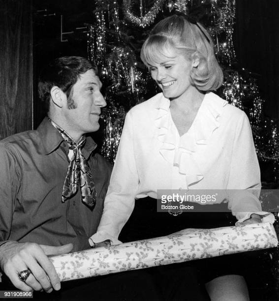 Boston Celtics John Havlicek left and Beth Havlicek right pose for a photo during the annual Christmas party at the Boston Garden Dec 22 1969