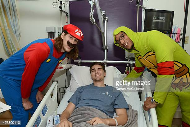 Boston Celtics Kelly Olynyk and Evan Turner spend time with John at Boston Children's Hospital October 24 2014 in Boston Massachusetts