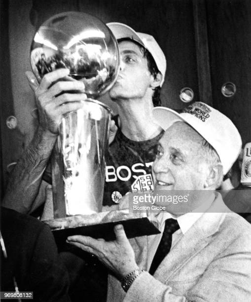 Boston Celtics' Kevin McHale kisses the championship trophy held by Celtics president Red Auerbach following the team's victory over the Houston...