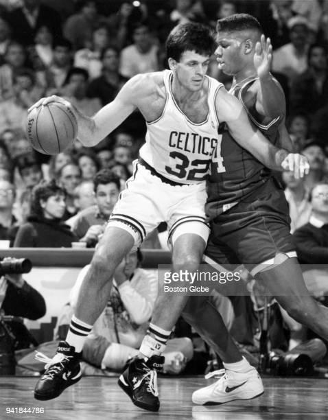 Boston Celtics Kevin McHale left dribbles around Charlotte Hornets JR Reid right during a game at the Boston Garden Nov 1 1991