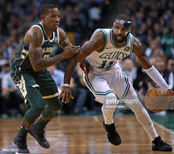 Boston Celtics' Kyrie Irving, right, drives past the Bucks' Eric Bledsoe during the first half. The Boston Celtics host the Milwaukee Bucks in a...