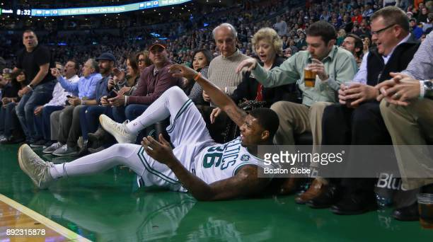 Boston Celtics' Marcus Smart hits the floor in front of some courtside fans as he chases the ball during the second quarter The Boston Celtics host...