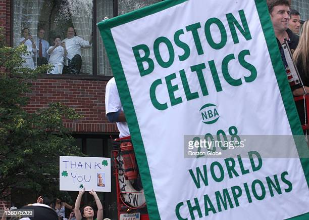 Boston Celtics owner Wyc Grossbeck top right holds the world championship banner as the Celtics rolling rally parade passes the Four Seasons Hotel on...