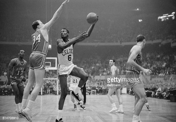 Boston Celtics' player Bill Russell hooks a shot during the NBA championship's final game in 1960 against the Saint Louis Hawks