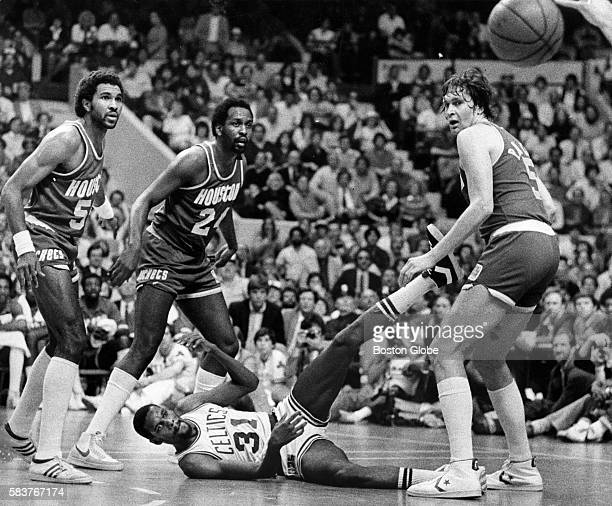 Boston Celtics player Cedric Maxwell center gets a pass off from the ground around Houston Rockets players Robert Reid Moses Malone and Billy Paultz...