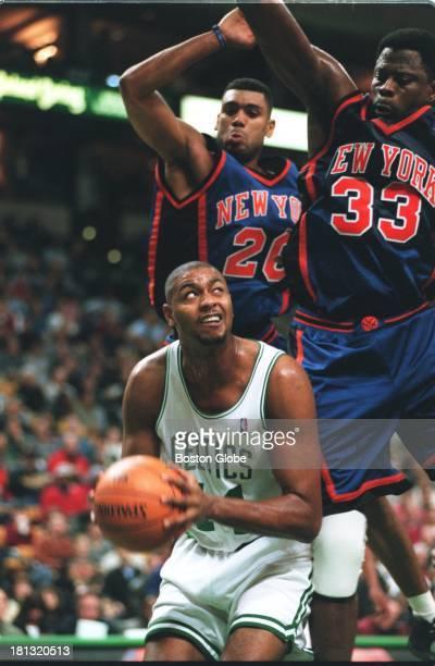 Boston Celtics player Eric Riley prepares to shoot beneath the New York Knicks' Allan Houston and Patrick Ewing