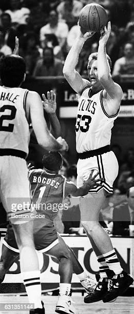 Boston Celtics player Larry Bird passes over Charlotte Hornets players Muggsy Bogues during a game at Boston Garden on Feb 6 1991