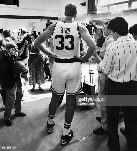 Boston Celtics player Larry Bird talks to the media while a child waits for an autograph during media day in Boston on Oct 4 1991