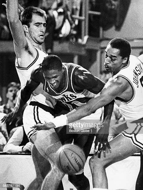 Boston Celtics players Fred Roberts left and Dennis Johnson right try to stop Atlanta Hawks player Dominque Wilkins from getting to the ball during a...