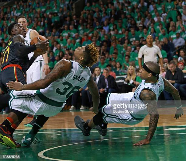 Boston Celtics players Marcus Smart and Isaiah Thomas hit the parquet while defending Atlanta Hawks guard Dennis Schroder in the first half of Game 3...