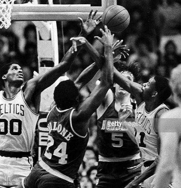 Boston Celtics players Robert Parish and Cedric Maxwell battle Houston Rockets players Moses Malone and Billy Paultz for the ball during a game at...