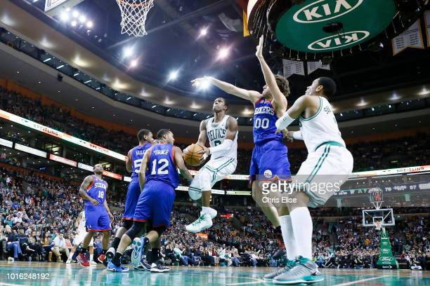 Boston Celtics point guard Rajon Rondo goes to the basket for the layup past Philadelphia 76ers center Spencer Hawes and Philadelphia 76ers small...