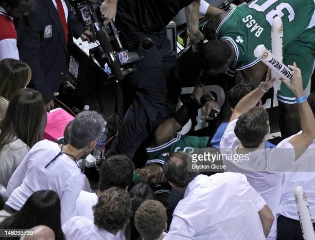 Boston Celtics power forward Brandon Bass checks on the condition of Boston Celtics point guard Rajon Rondo after Rondo took a hard fall after having...