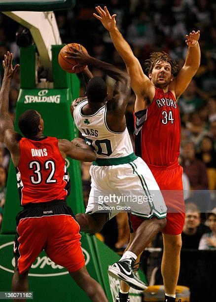 Boston Celtics power forward Brandon Bass splits the defense of Toronto Raptors power forward Ed Davis and Toronto Raptors center Aaron Gray on this...