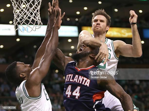 Boston Celtics power forward Shavlik Randolph makes contact with Atlanta Hawks power forward Ivan Johnson after seating away a shot attempt by...