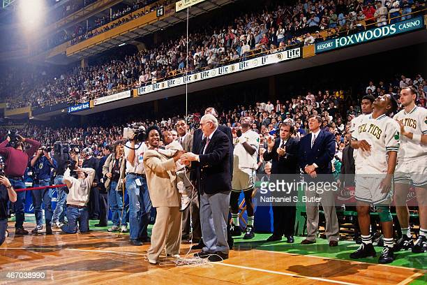 Boston Celtics President and Chairman Red Auerbach raise Reggie Lewis' jersey to the rafters during Reggie Lewis Night on March 22 1995 at the Boston...