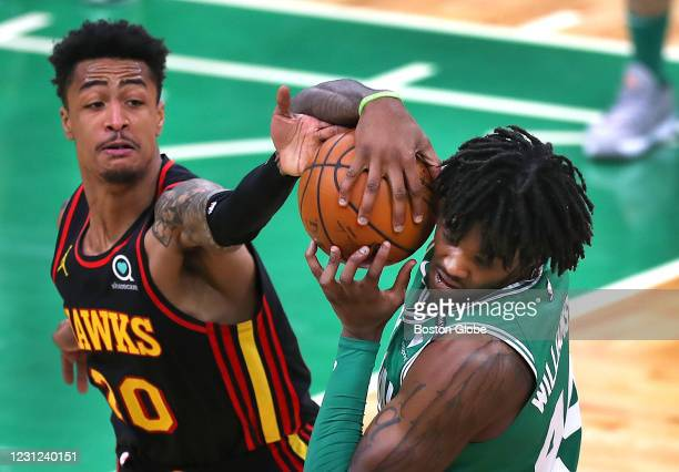 Boston Celtics' Robert Williams grabs control of a pass as Atlanta Hawks' John Collins gets a hand on the ball in the third quarter. The Boston...