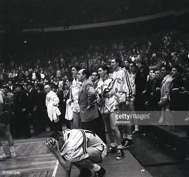 Boston Celtics' rookie Tom Heinsohn can't bear to look at the final seconds of action while coach Red Auerback watches the clock during a National...