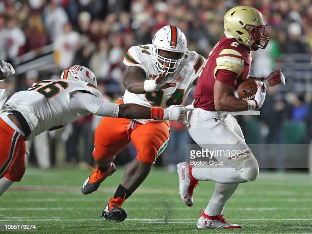 Boston College Eagles' AJ Dillon breaks tackles from University of Miami Hurricanes' Michael Pinckney and Tito Odenigbo during the first half The...