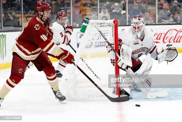 Boston College Eagles forward Christopher Brown centers the puck past UMASS Minutemen goalie Filip Lindberg during a Hockey East semifinal game...