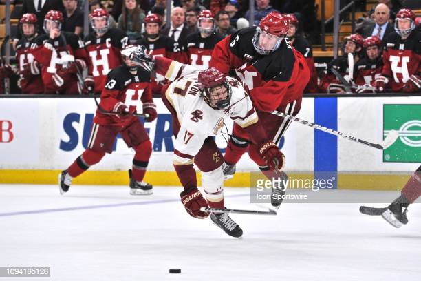 Boston College Eagles forward David Cotton its separated from the puck by Harvard Crimson forward Colton Kerfoot . During the Boston College Eagles...