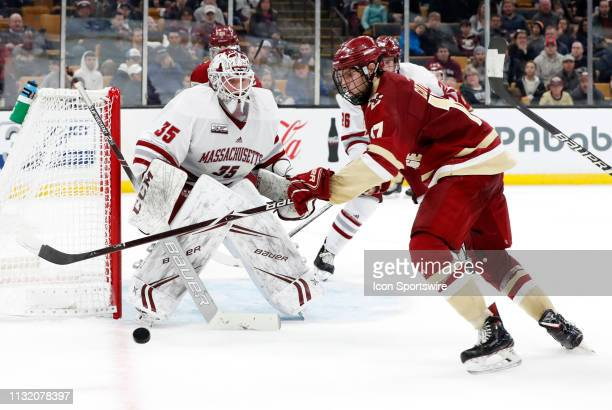 Boston College Eagles forward David Cotton tries to control the puck watched by UMASS Minutemen goalie Filip Lindberg during a Hockey East semifinal...
