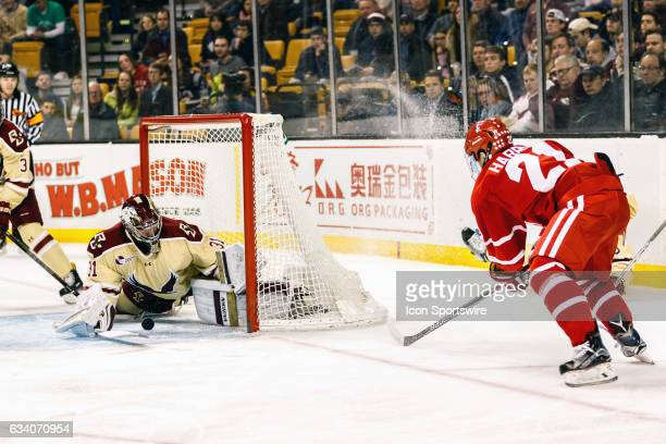 Boston College Eagles goaltender Joseph Woll blocks a shot by Boston University Terriers forward Patrick Harper but leaves the puck loose in front of...