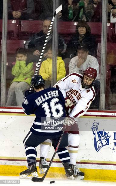 Boston College Eagles men's ice hockey player Ian McCoshen plays the puck as he is checked into the boards by University of New Hampshire Wildcats...